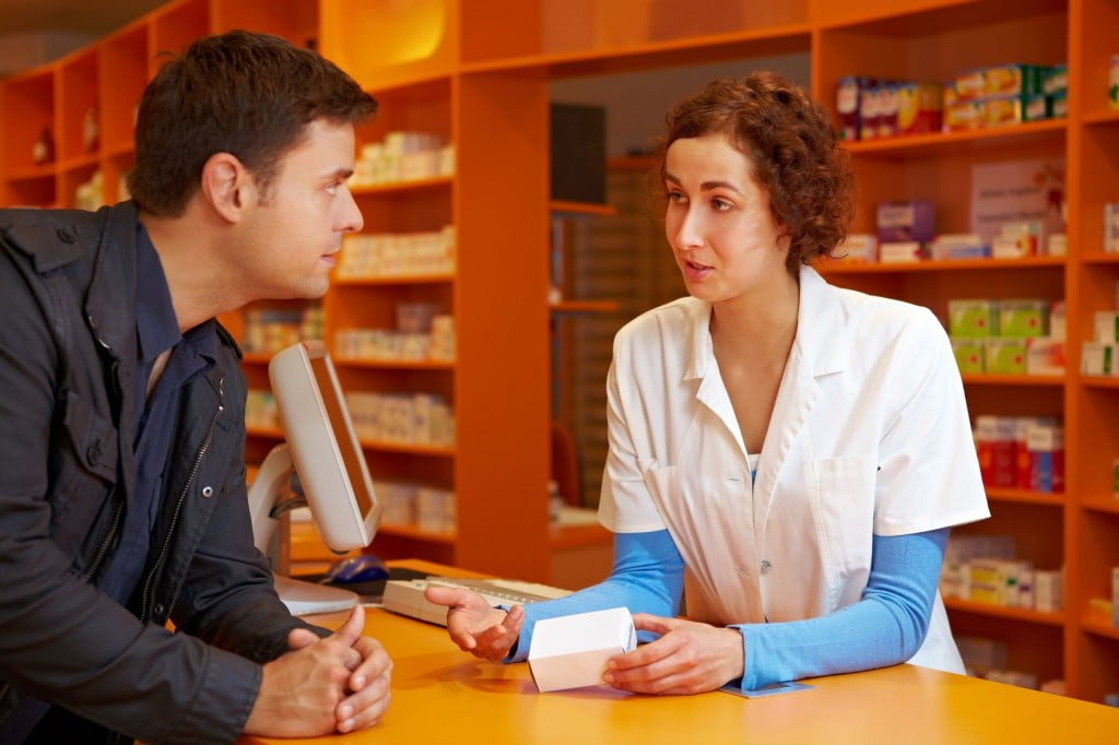 man talking to woman pharmacist