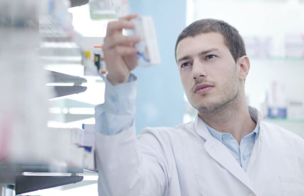 young male doctor looking at pill packet