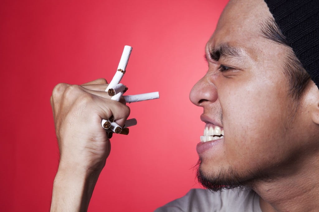 man holding some cigarettes trying to stop from smoking