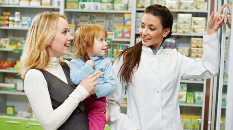 woman pharmacist helping a mother and her daughter