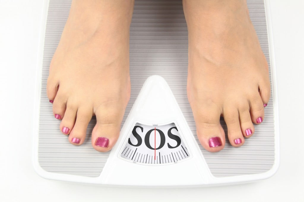 "feet on scales,which say ""SOS"""