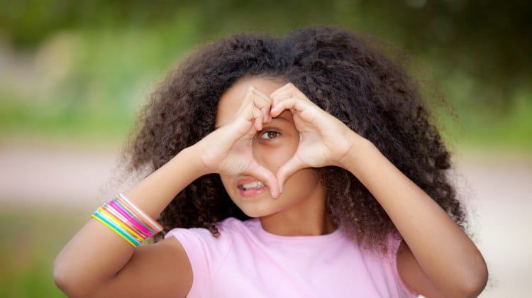 heartkids: teenage girl makes heart shape with hands over her eye