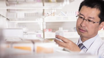 male pharmacist looking at pills