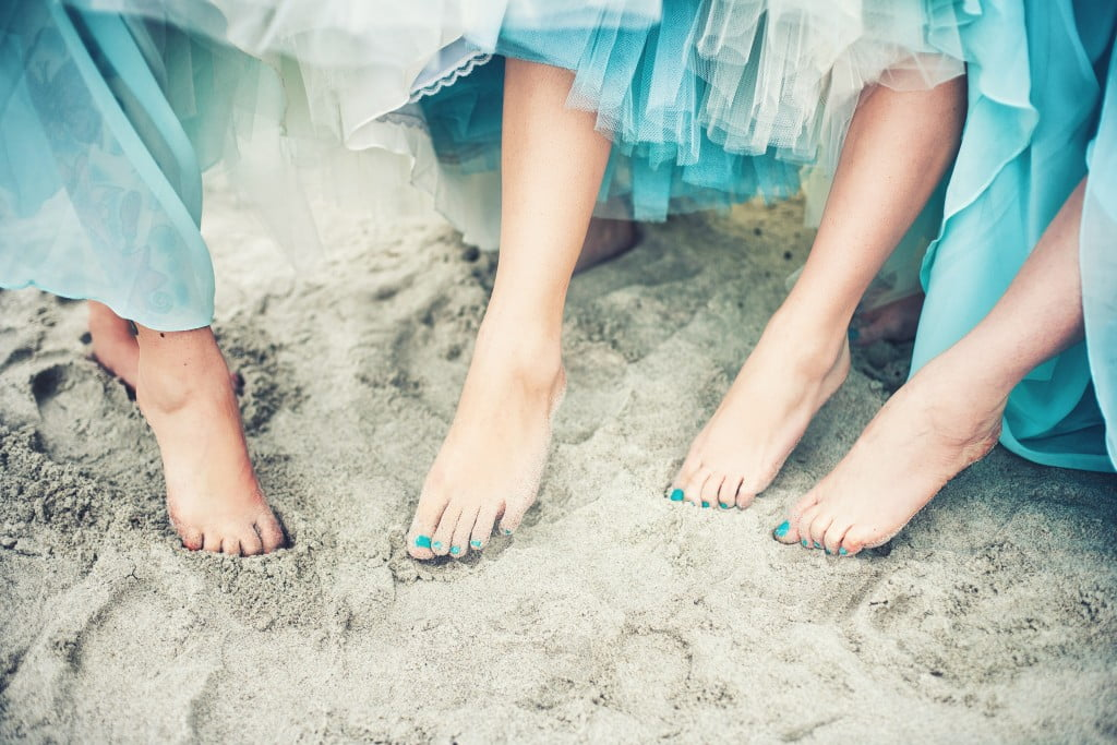 ovarian cancer symptoms: women in teal dresses at beach with teal toenail polish
