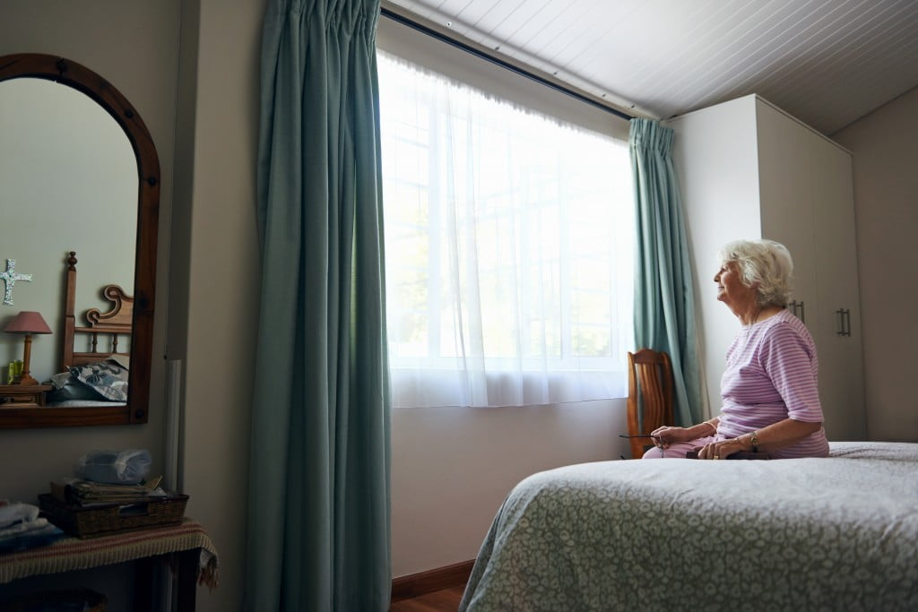 old lady sits on bed and looks out window