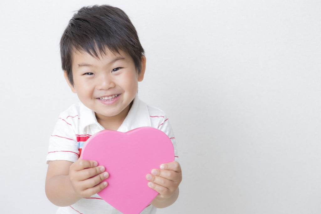 Congenital heart disease: little boy holding pink cardboard heart