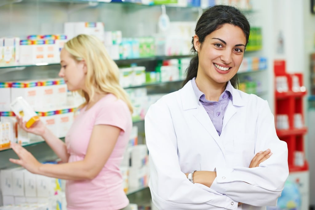 Community pharmacy: smiling pharmacist in shop