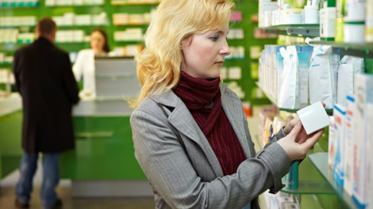 pharmacy IRI-Aztec report: blonde woman browses pharmacy shelves