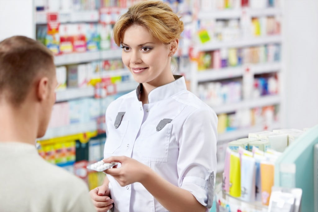 Young pharmacists – pharmacist gives medicine to patient over counter