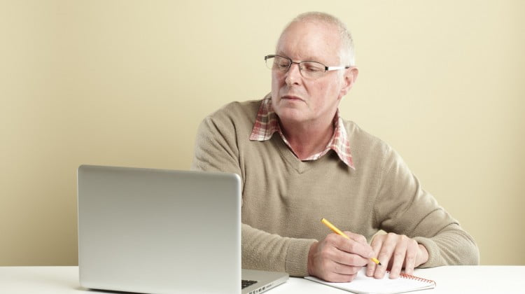 health websites: man reading laptop and making notes
