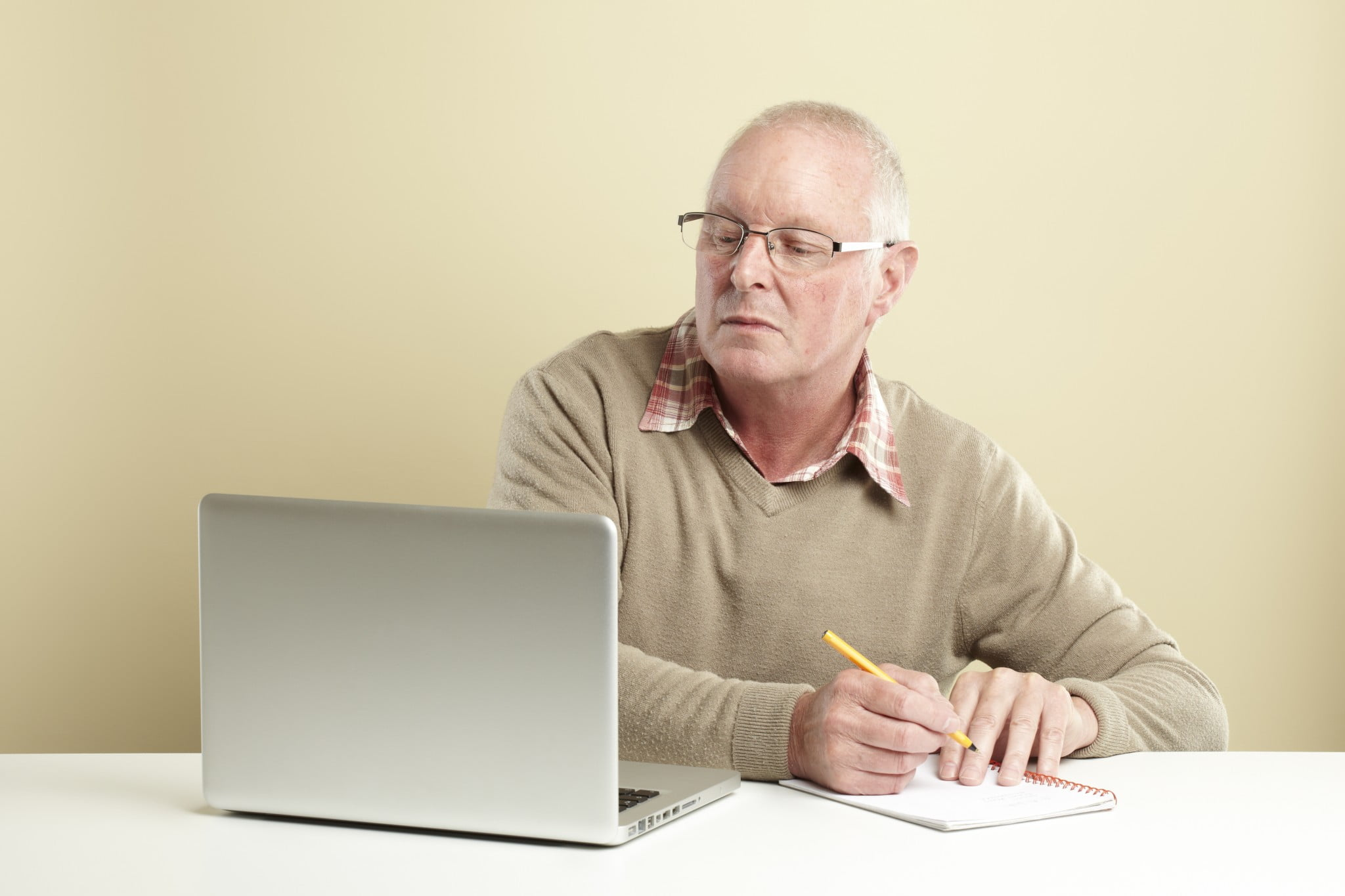 man reading laptop and making notes