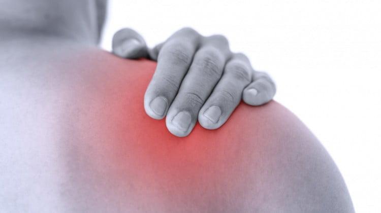 Man rubs sore shoulder