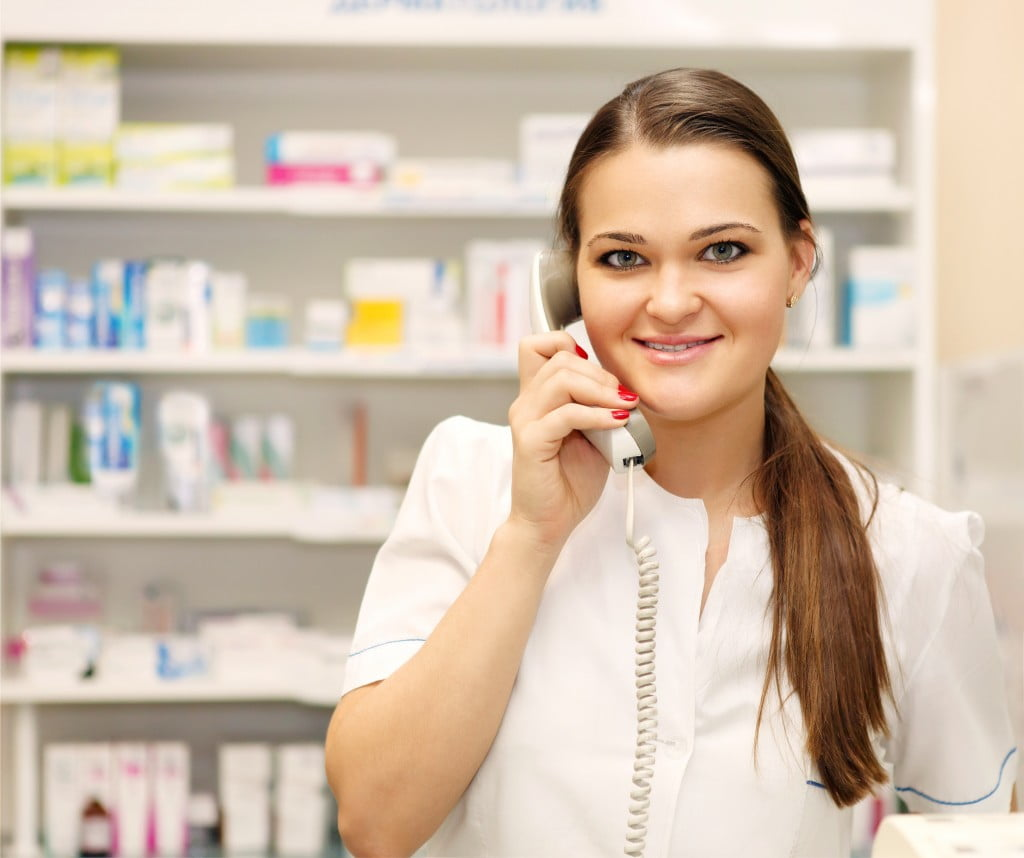 Pharmacists' Support Service: young pharmacist on the phone, smiling