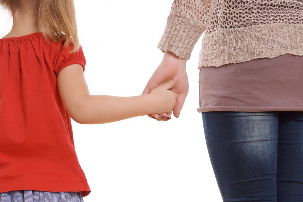 glaucoma family risk: mother holding hands with little blonde girl