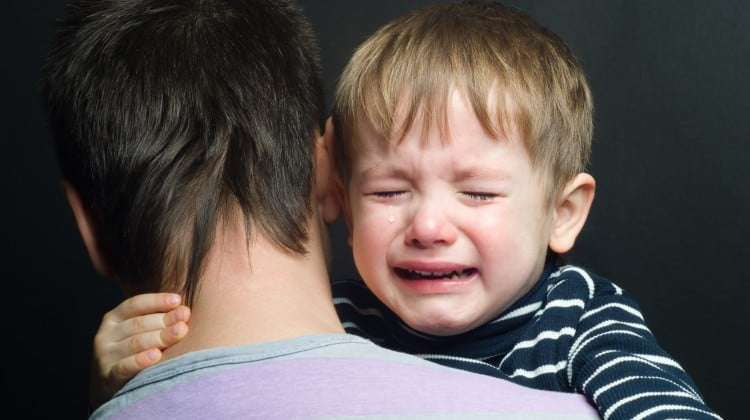 arthritis: little boy crying on father's shoulder