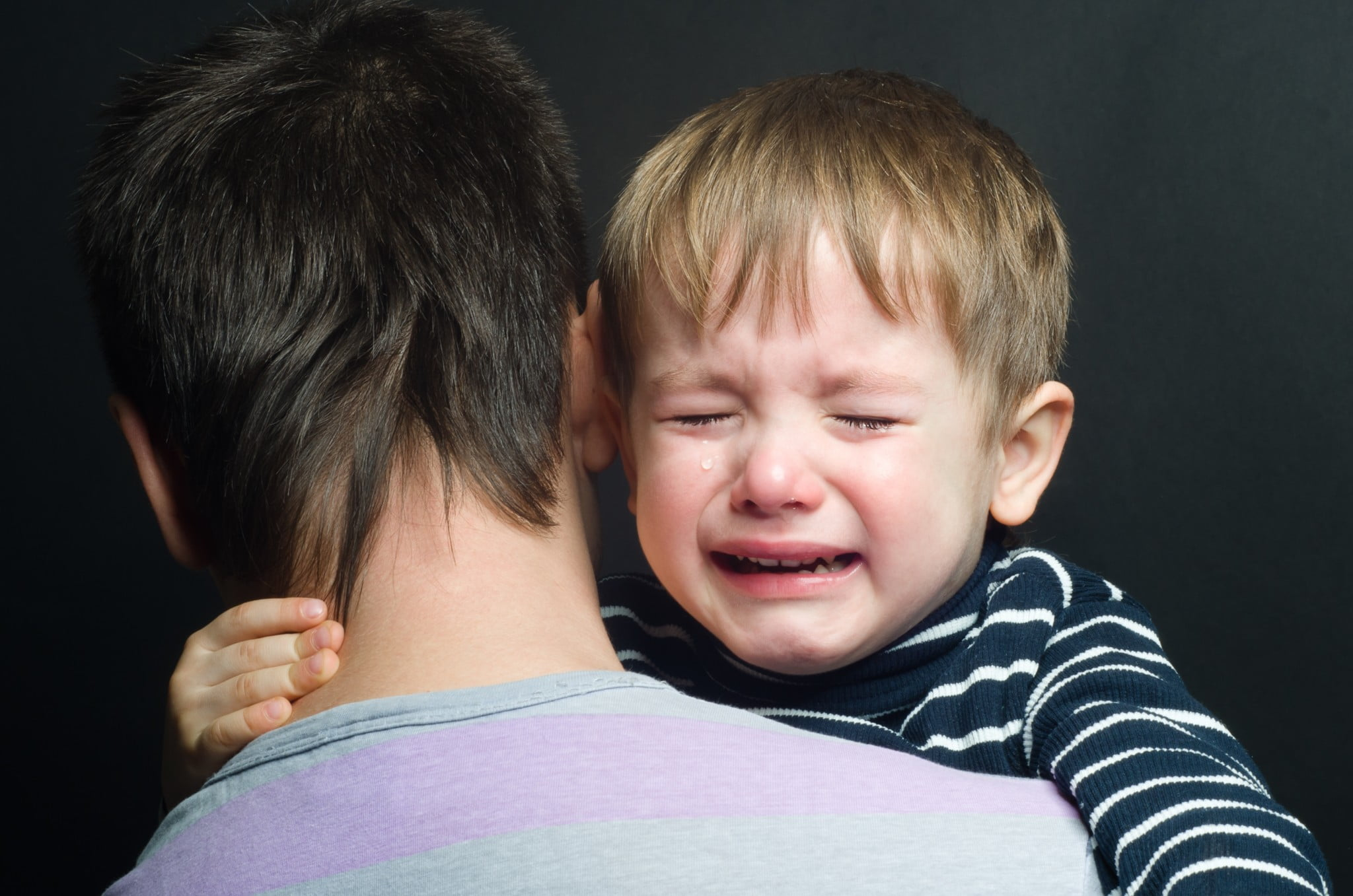 little boy crying on father's shoulder