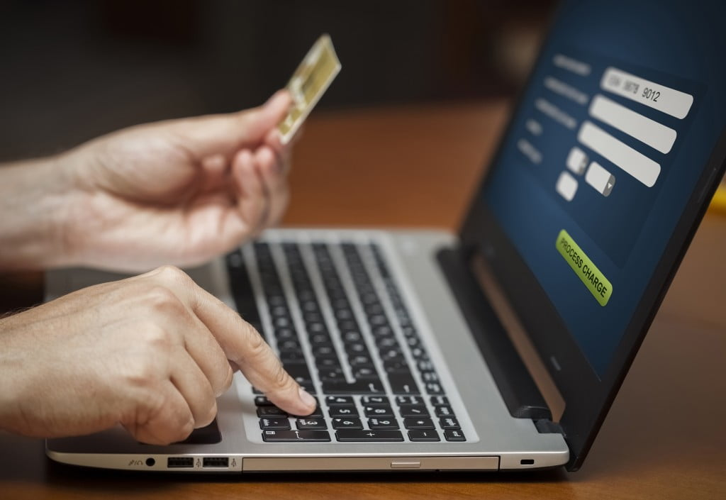 online shopping danger: hands, laptop, credit card
