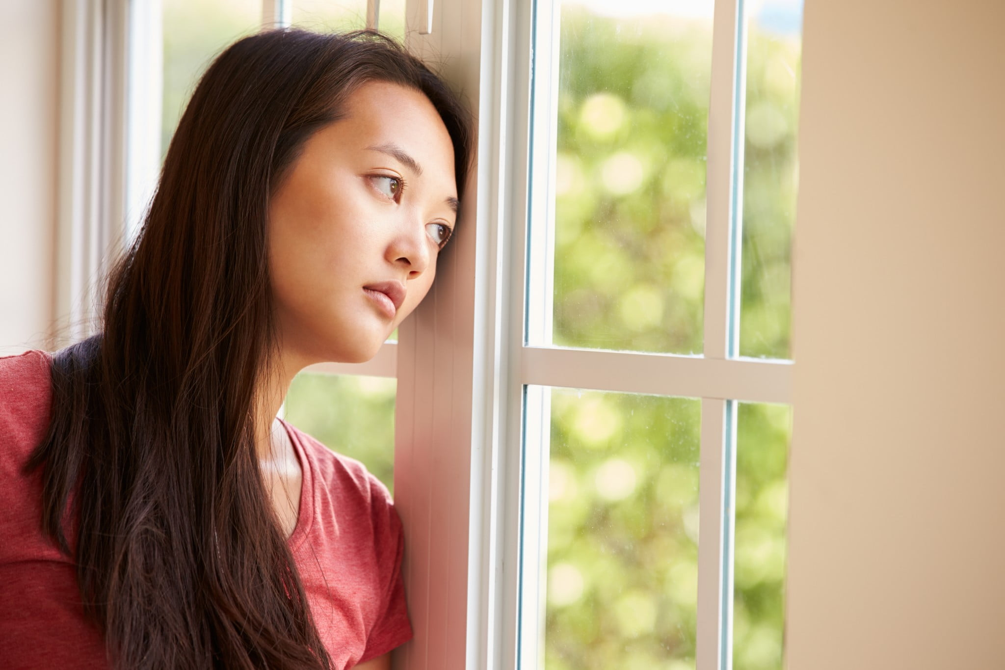 woman gazes out of window