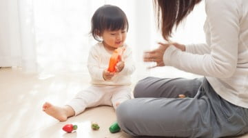 FIP launches MCHN resources: little girl plays with toys next to mother