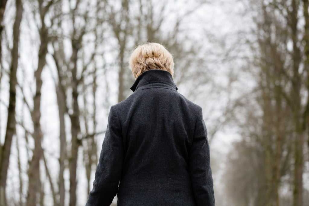 Polycystic Ovary Syndrome: woman walks away from camera into winter trees
