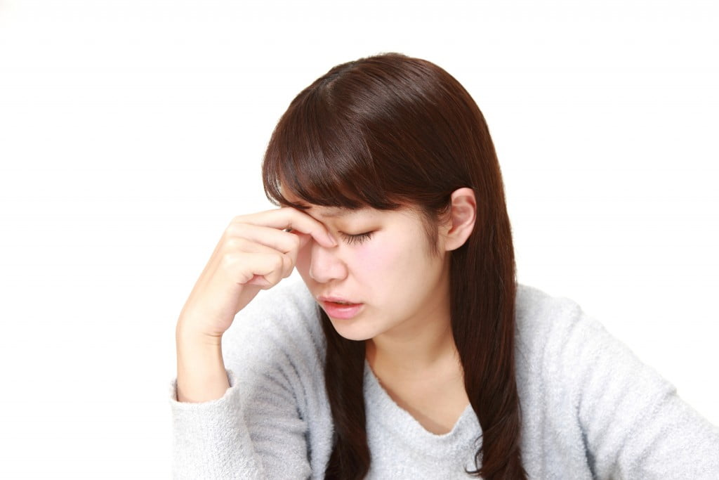 fatigue: young woman looks down and pinches nose between eyes
