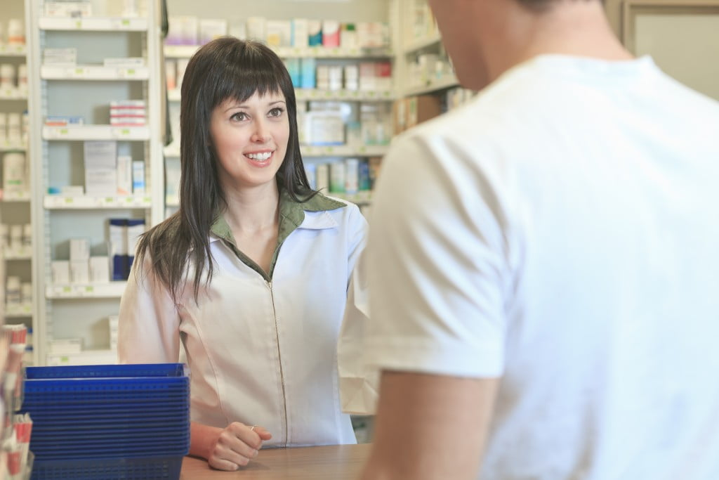 happy pharmacist serving customer