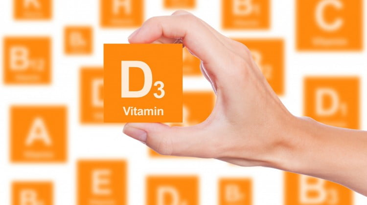 hand holds up orange square that says Vitamin D3