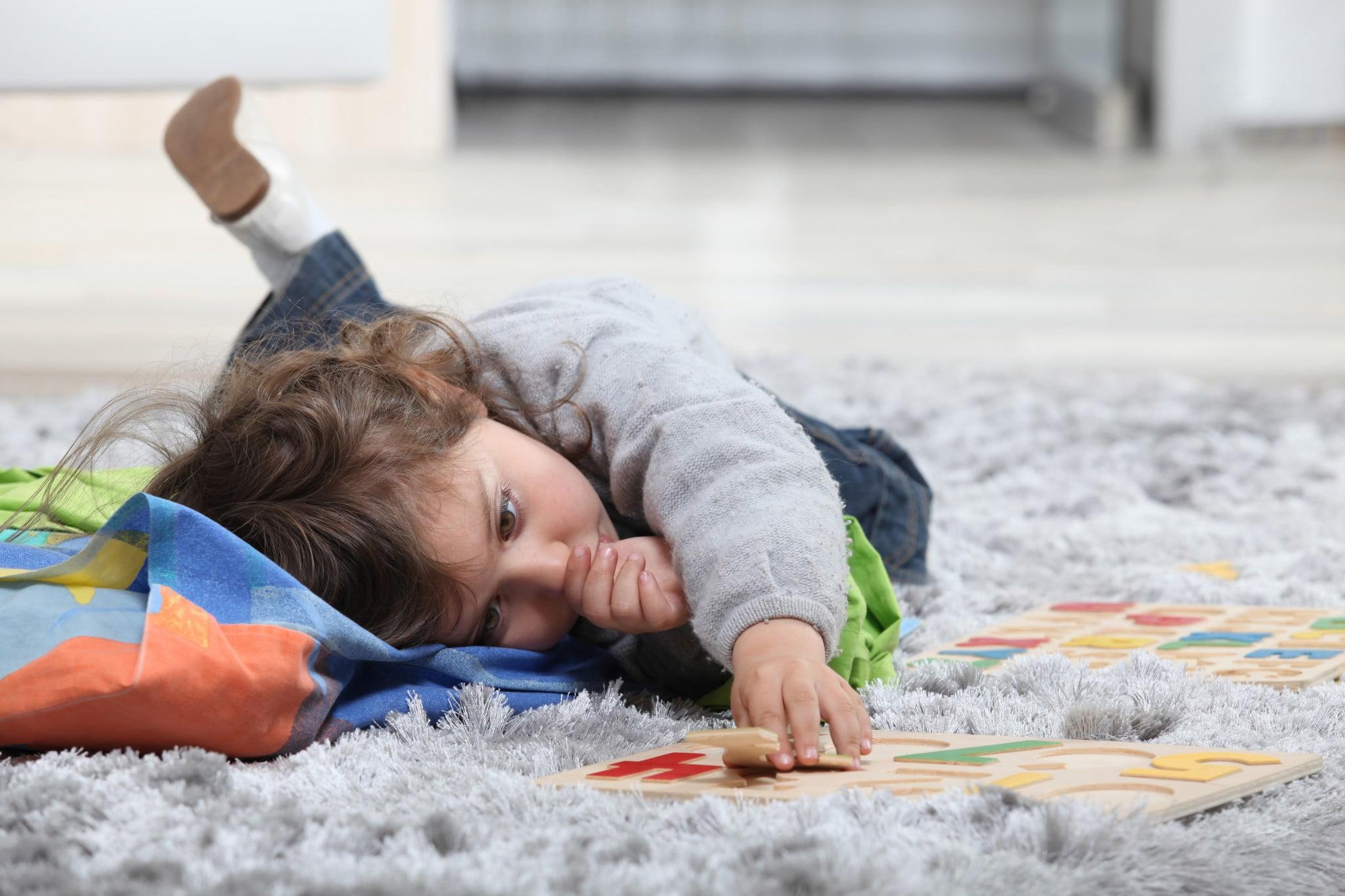 toddler plays on grey shag rug