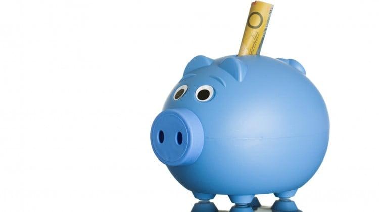 $50 note sticks out of blue piggybank