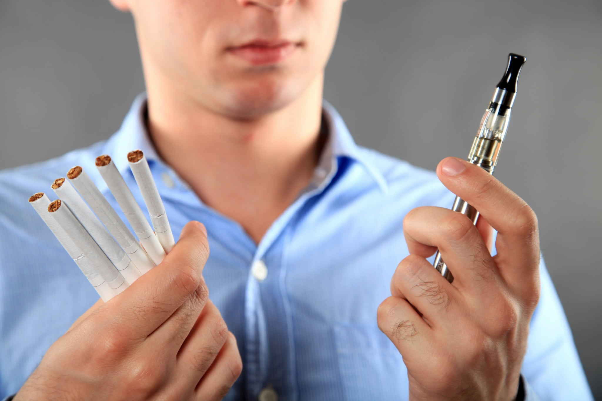 man with e-cigarette in one hand and six cigarettes in the other