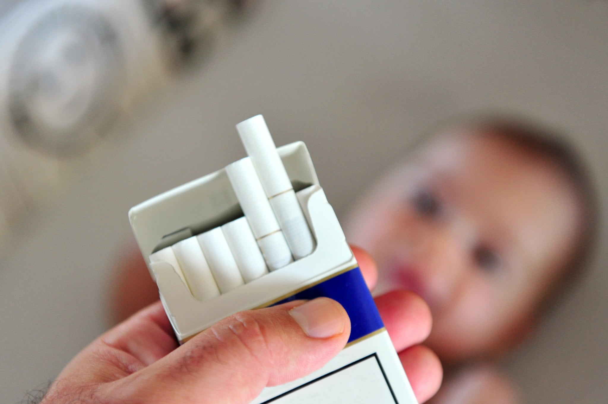 plain packaging, cigarette packet in front of baby