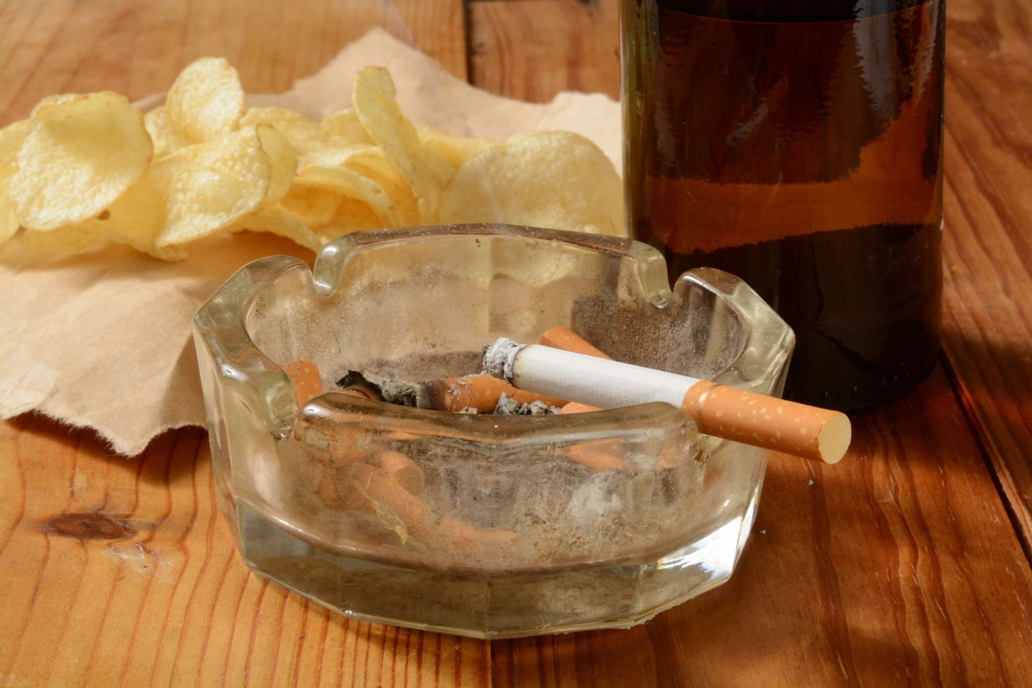 bad habits: cigarette smouldering in ashtray in front of crisps and beer
