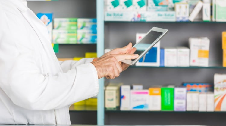 pharmacist with tablet in store