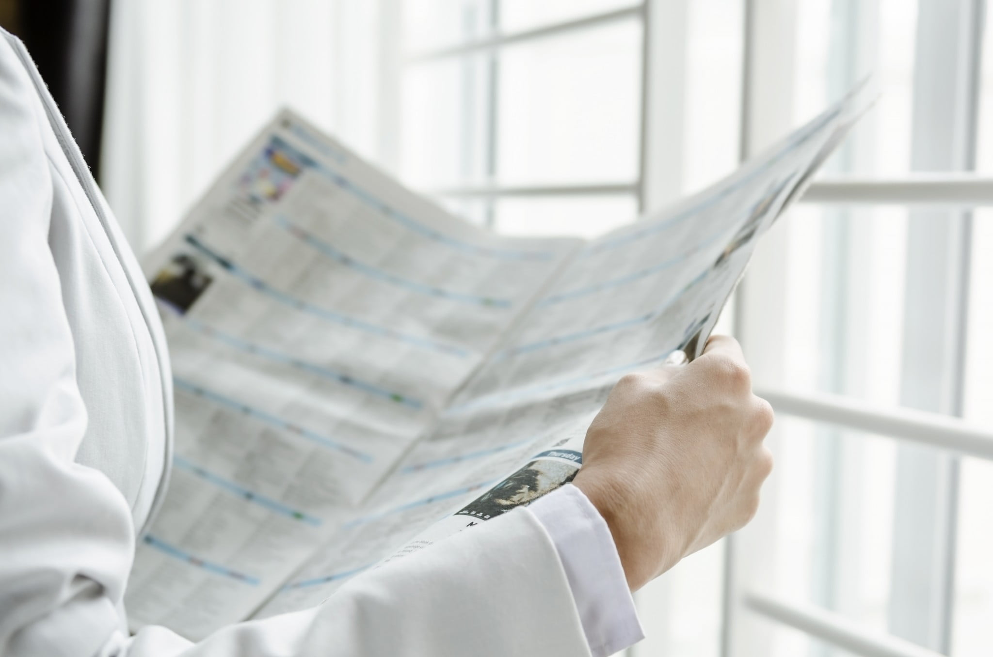 pharmacy worker reading newspaper