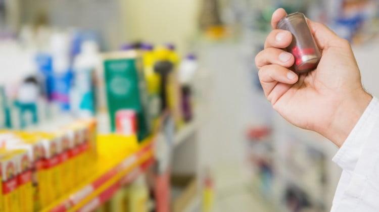 pharmacist holds up bottle