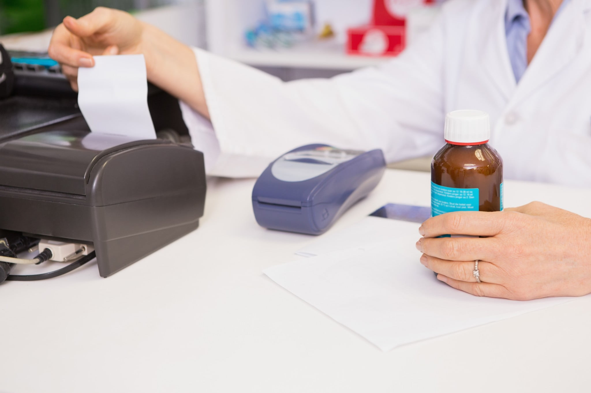 pharmacist at POS machine with bottle of medicine