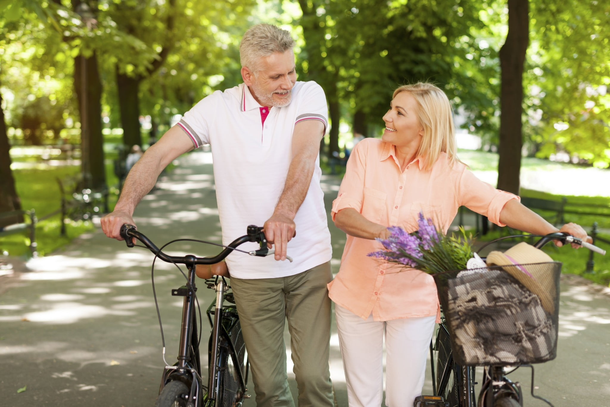elderly couple walking next to their bicycle