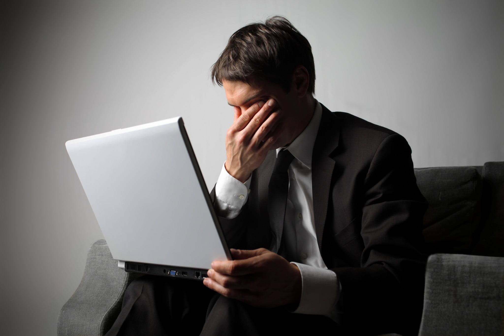 mental illness stigma: man in suit with laptop covers face