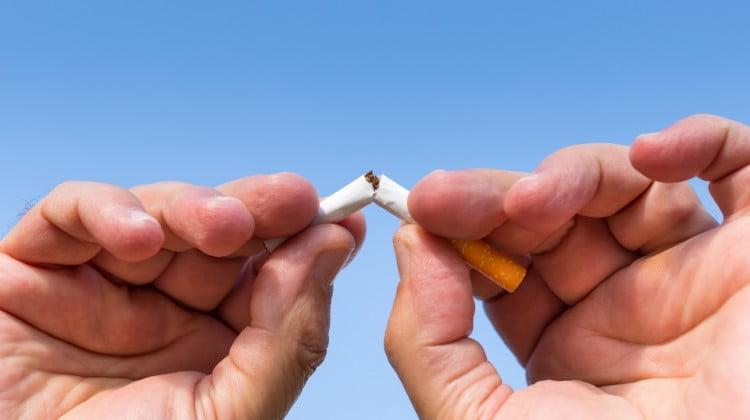 quit smoking: hands hold broken cigarette in front of blue sky
