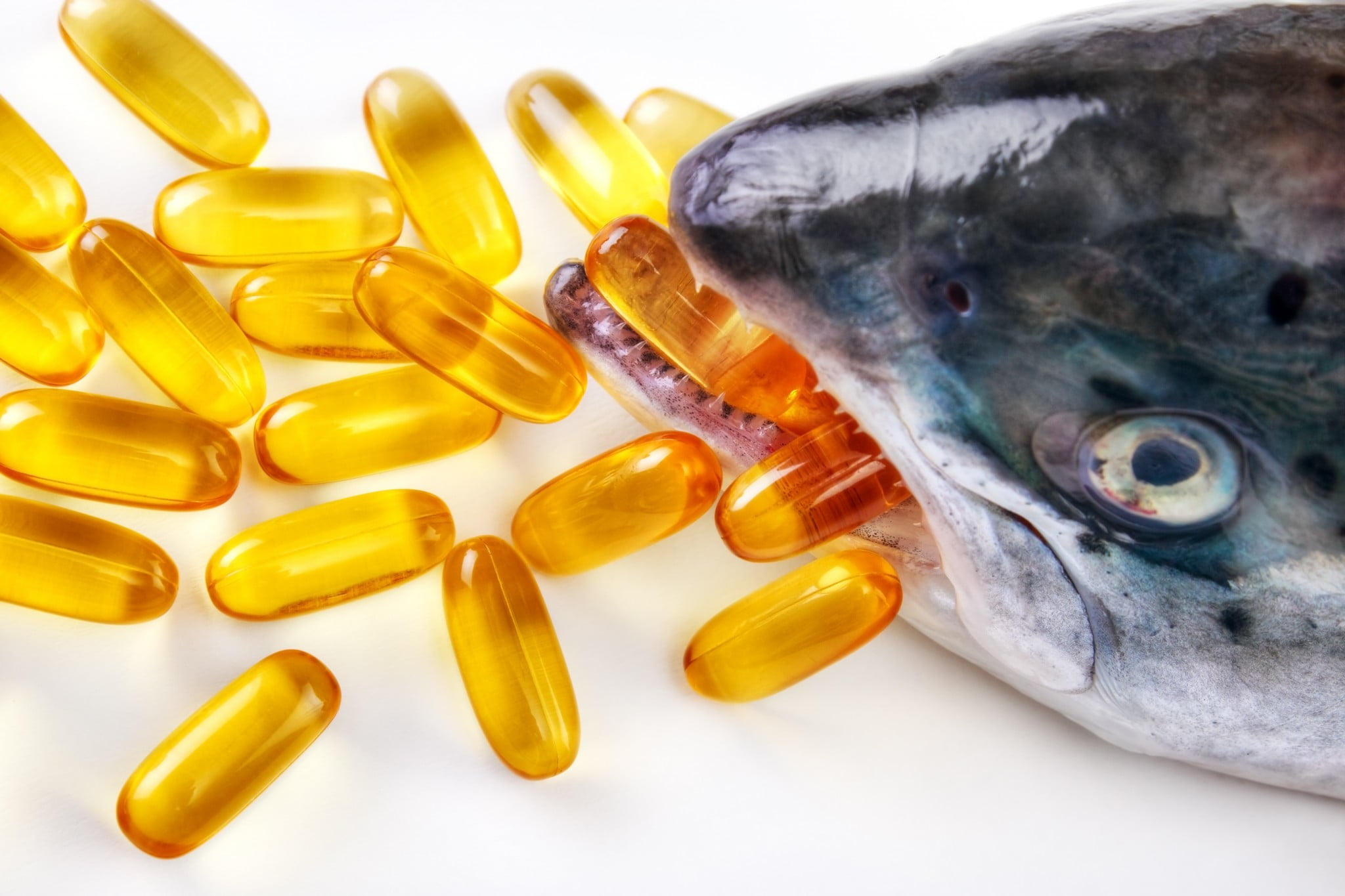 fish oil capsules in the mouth of a fish
