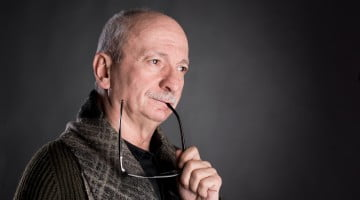 Parkinson's disease concept: senior man with grey moustache looks pensive, with ear of glasses in his mouth