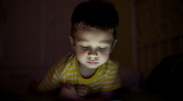 screen time: child in the dark with ipad