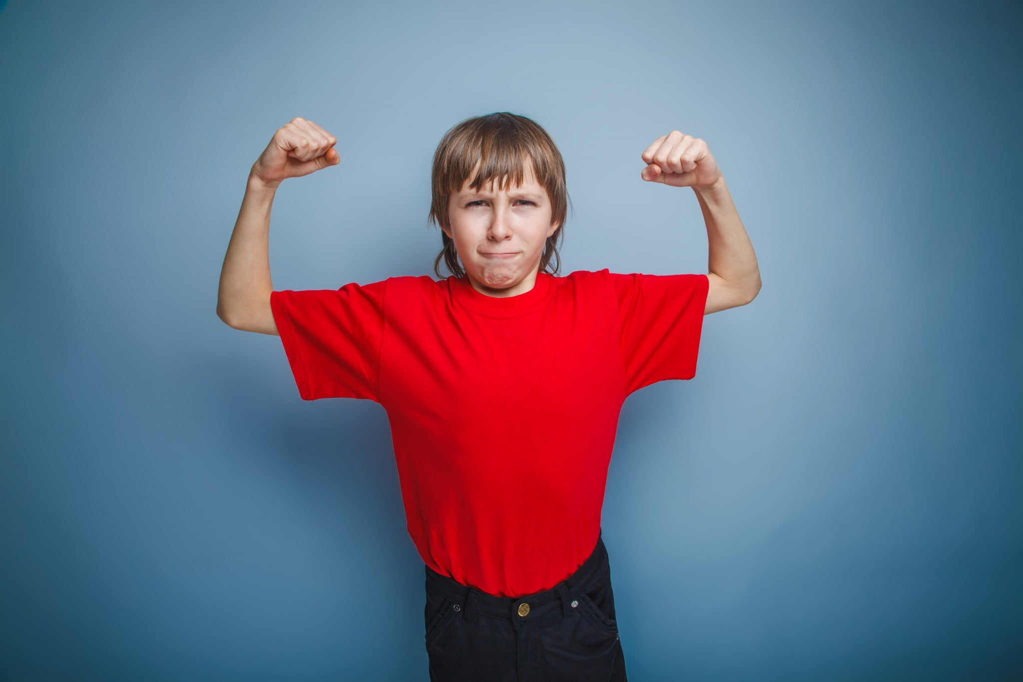 Boys and body image: young boy flexes skinny biceps