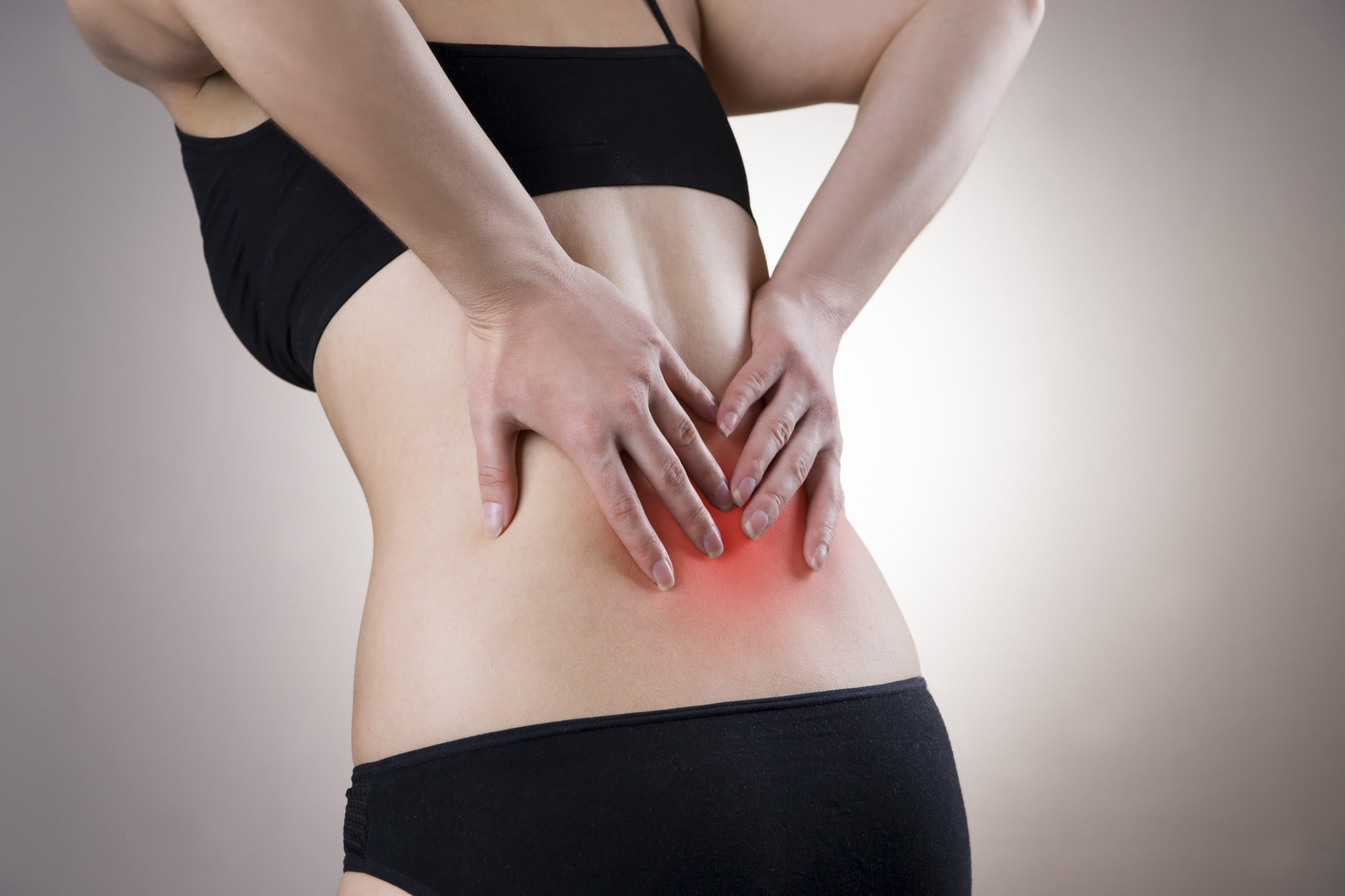 back pain: woman rubs lower back