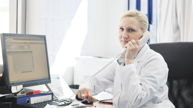 employee pharmacists: busy-looking pharmacist on hold on the phone