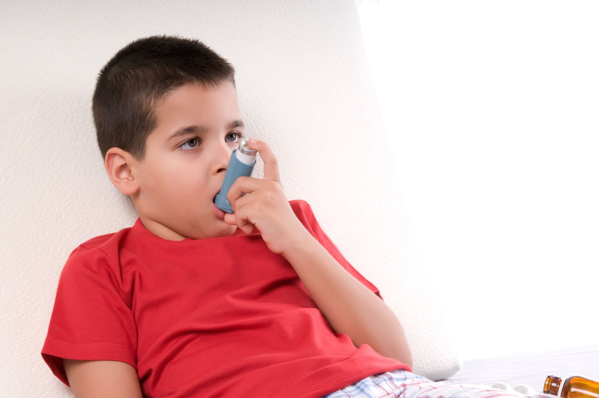 boy wtih asthma uses reliever puffer