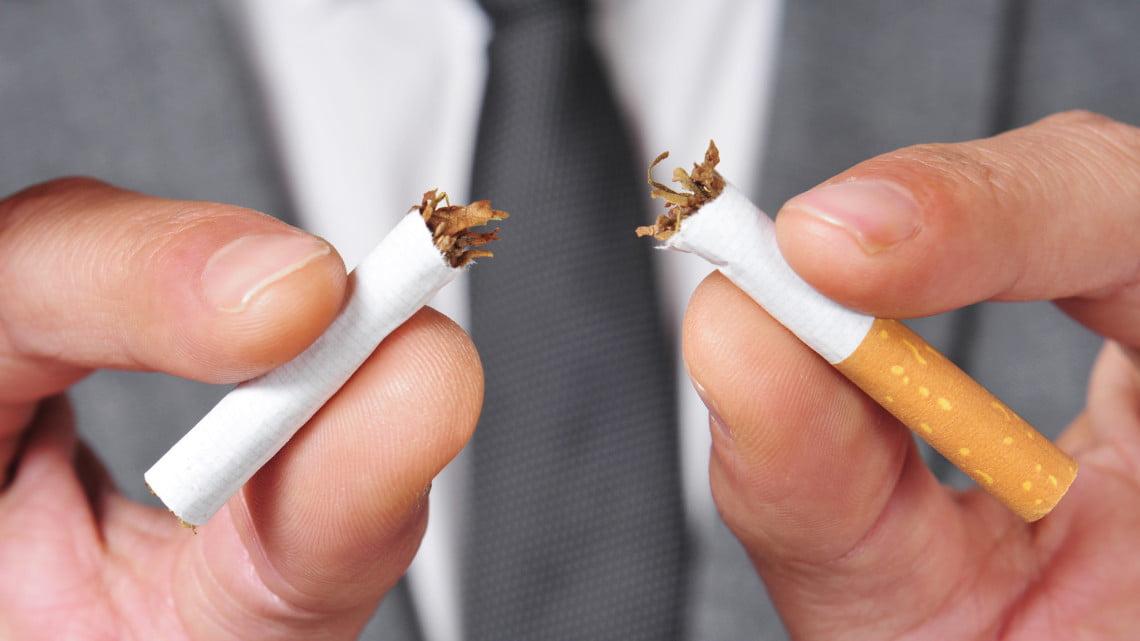 quit smoking: man breaks cigarette in half