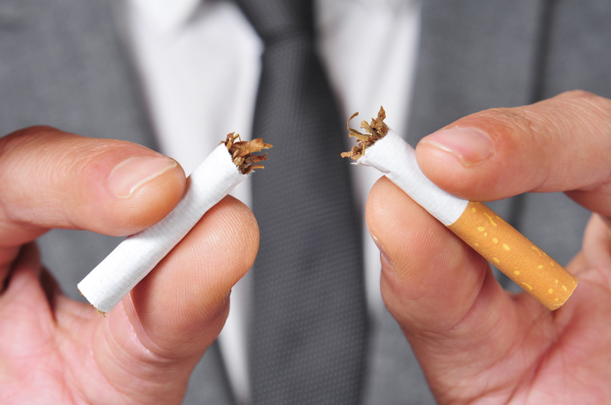 quit smoking: man breaks cigarette in half