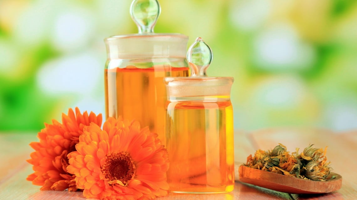 homoepathy: jars full of tincture and some orange flowers