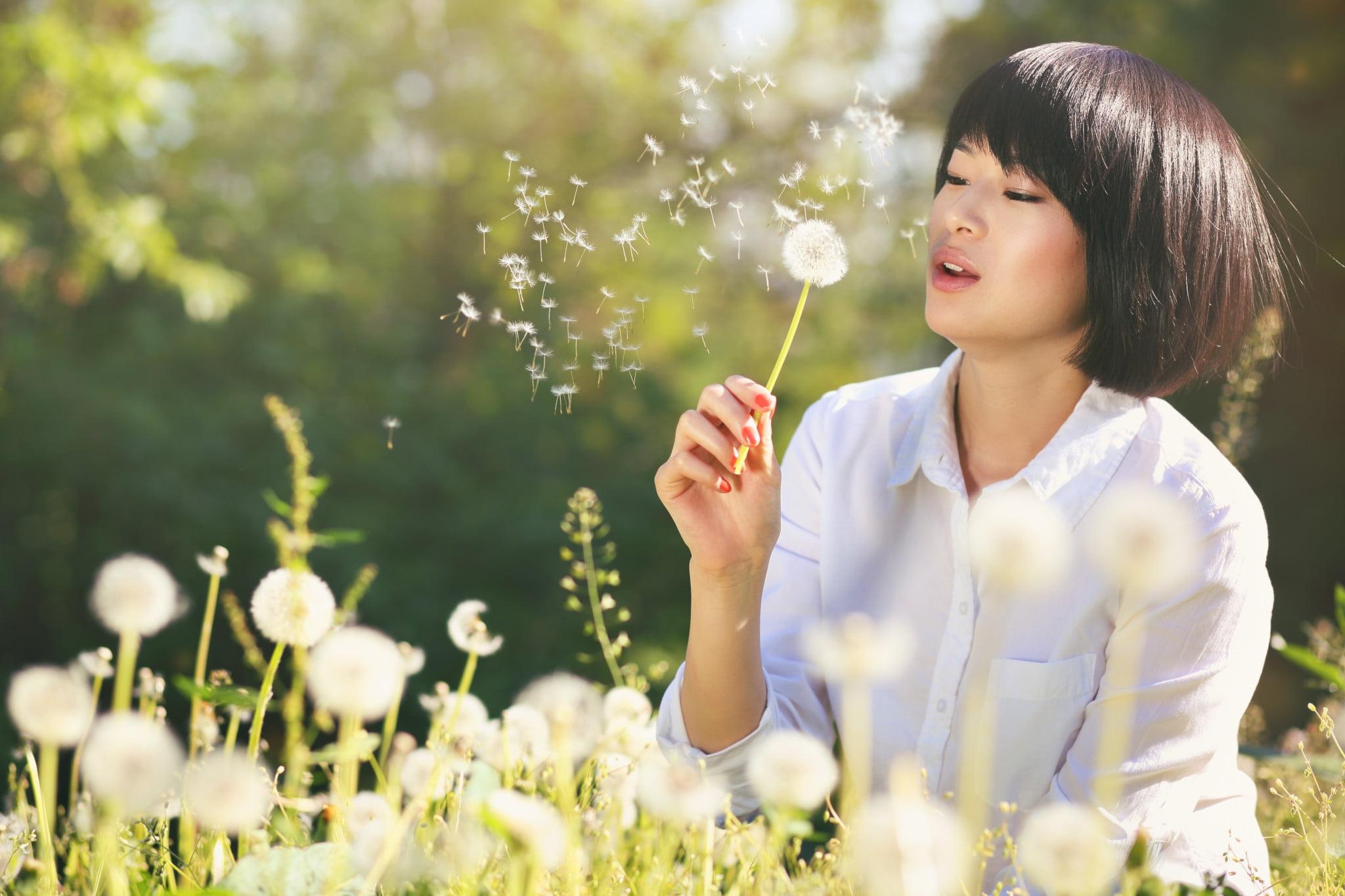 asthmatics - woman blowing dandelion